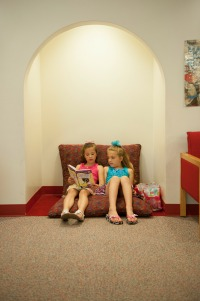 two girls reading in a nook in the Children's Library